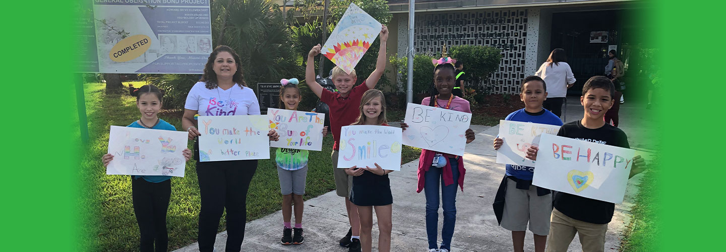councelor with students with signs that say be happy